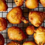Hush puppies freshly fried on a baking sheet.