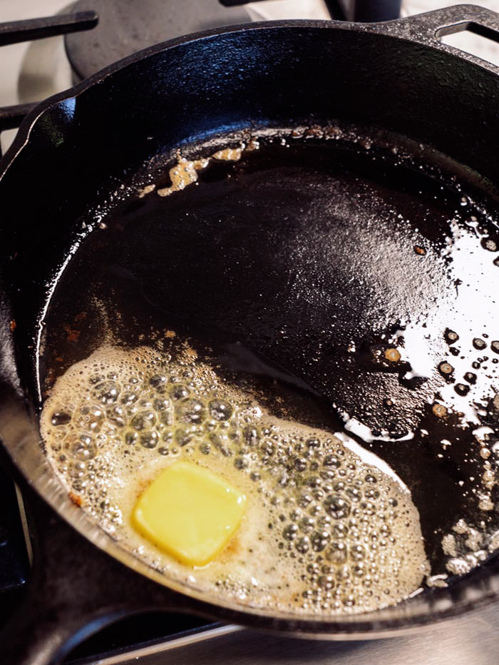 A close up of melting butter in a skillet.