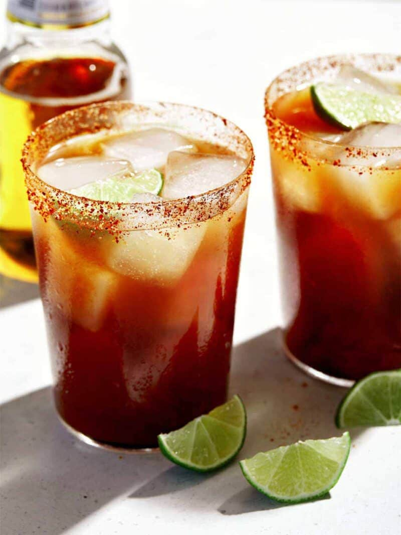 A close up of two glasses of Michelada with lime wedge garnish.