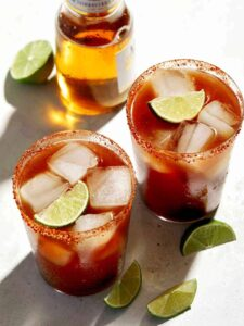 Beer bottle and glasses of Michelada with lime wedge garnish.