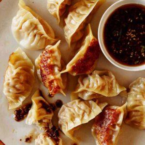 Panfried potstickers with ramekin of sauce.