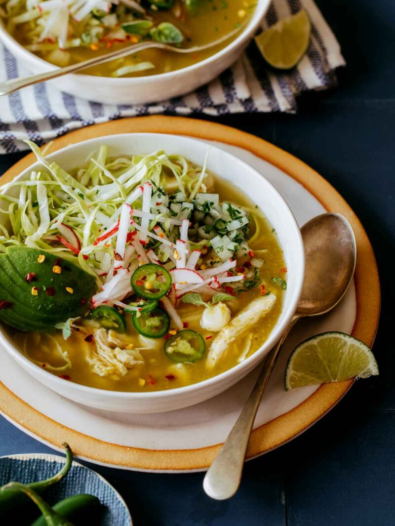 Pozole Verde de Pollo in two bowls with lime wedges on the side.