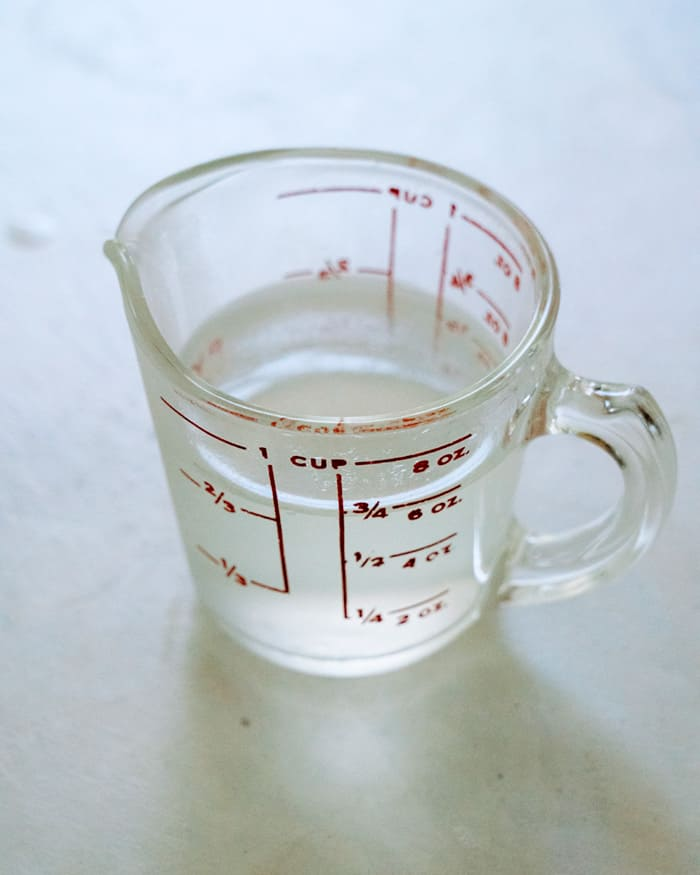Glass measuring cup with pasta water.