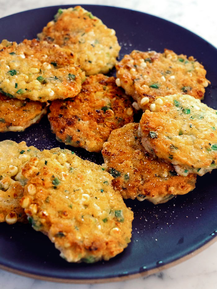 Corn cakes on a platter seasoned  with salt and pepper.