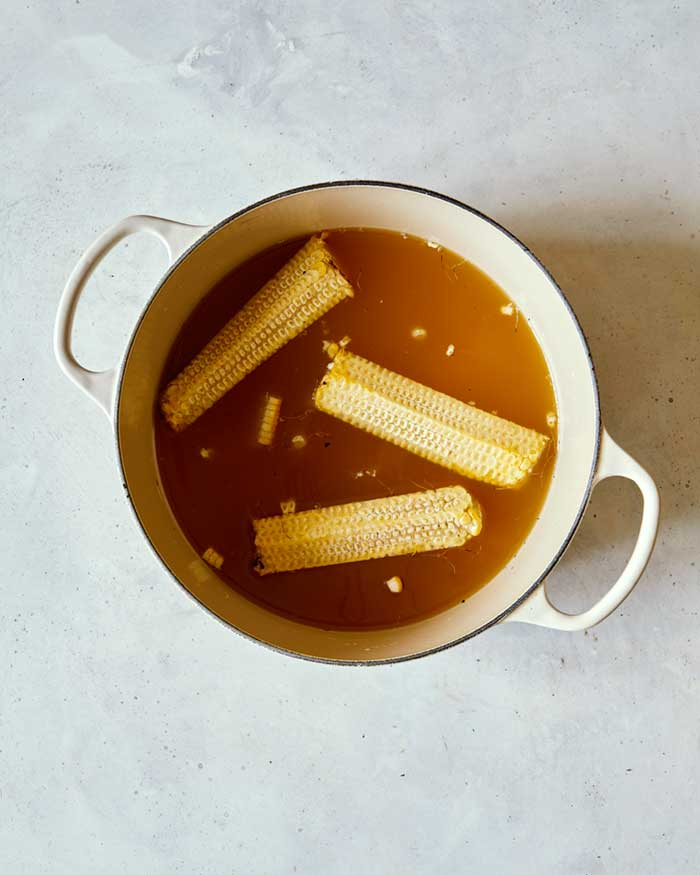 Corn cobs and kernels simmering in stock.