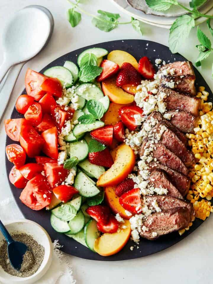 Summer steak salad on a black plate.