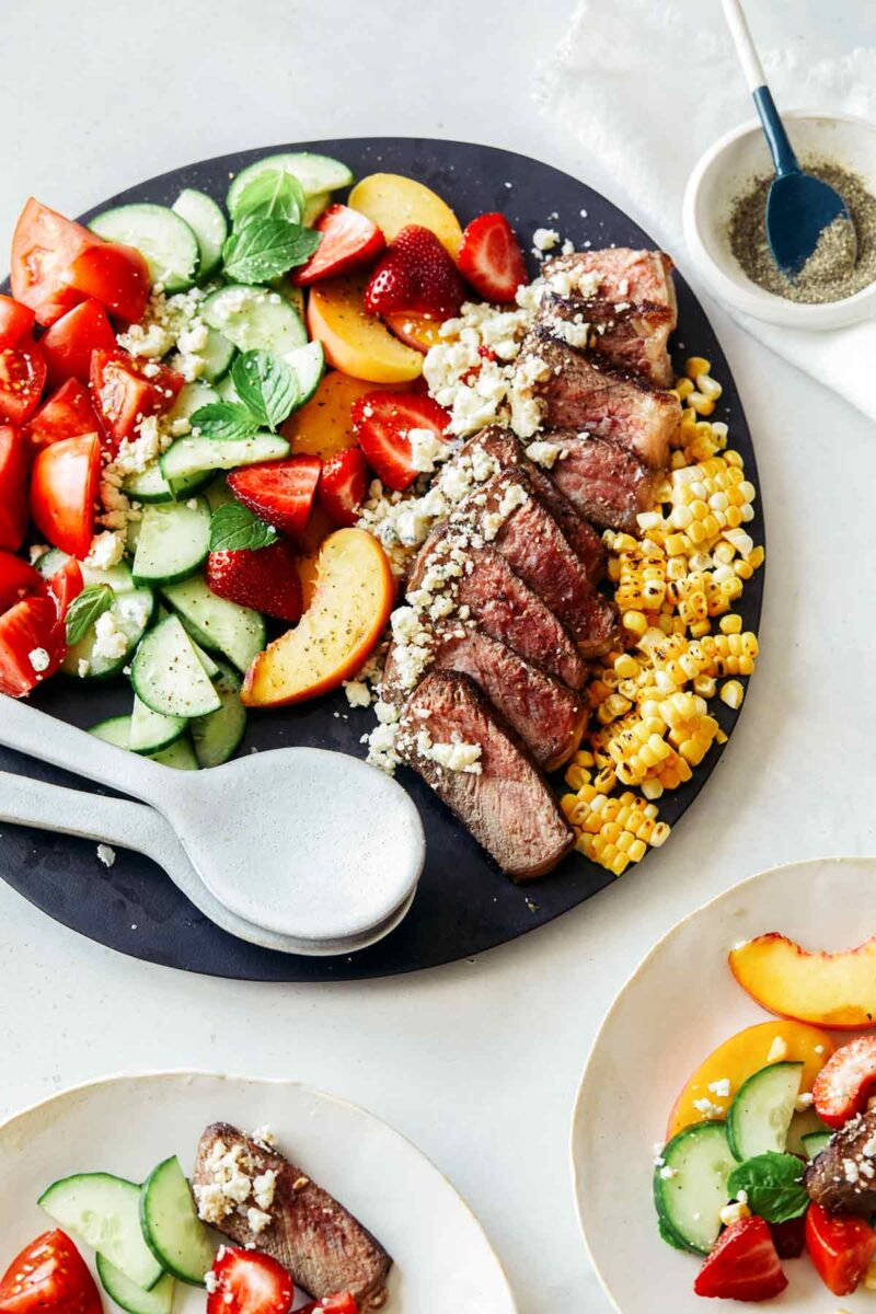 A steak salad on a platter with some served onto plates next to it.