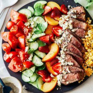 Summer steak salad on a black plate.