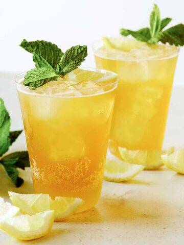 A glass of sparkling lemonade shandy with mint and lemon slice garnish.