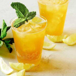 A glass of sparkling lemonade shandy with mint and lemon slice garnish.