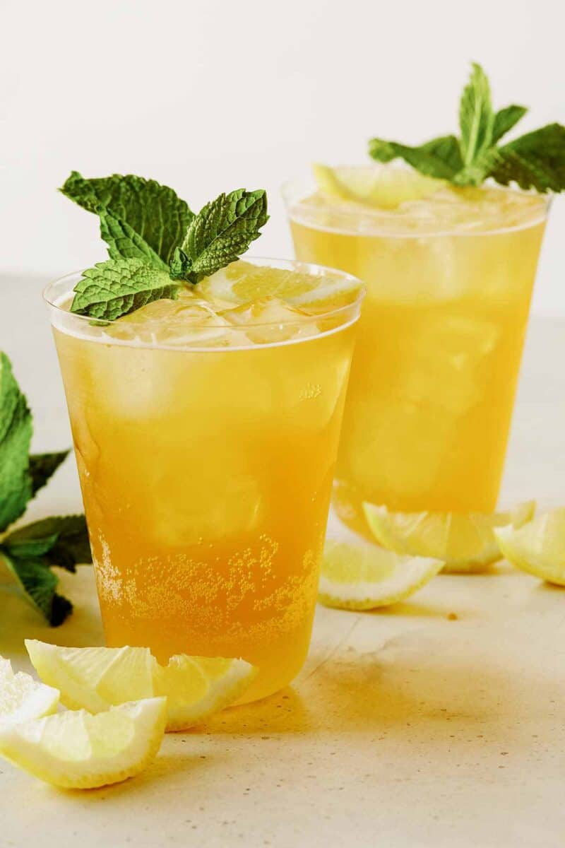 A close up of summer shandy cocktails with fresh mint and lemon wedges.