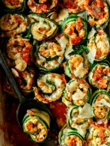 A close up of zucchini lasagna roll ups with a serving spoon.