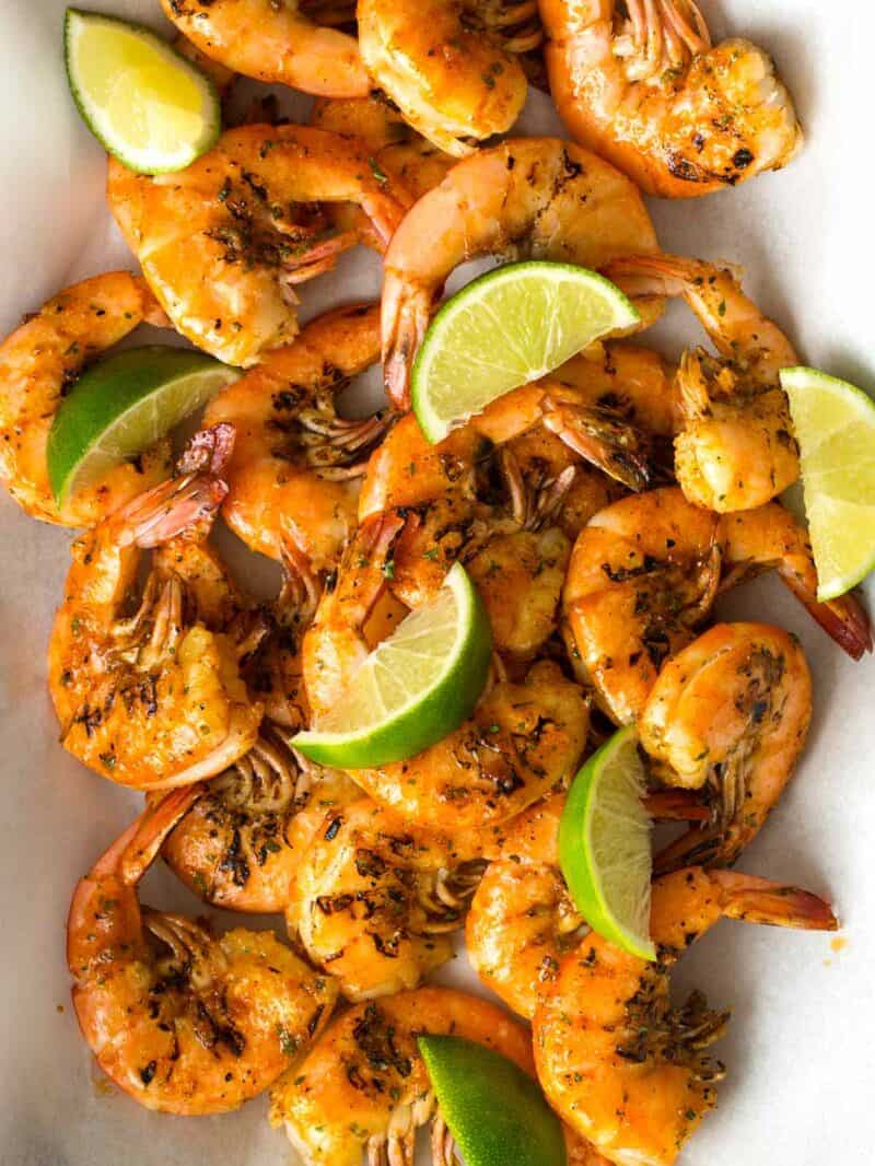Grilled peel and easy shrimp with lime wedges.
