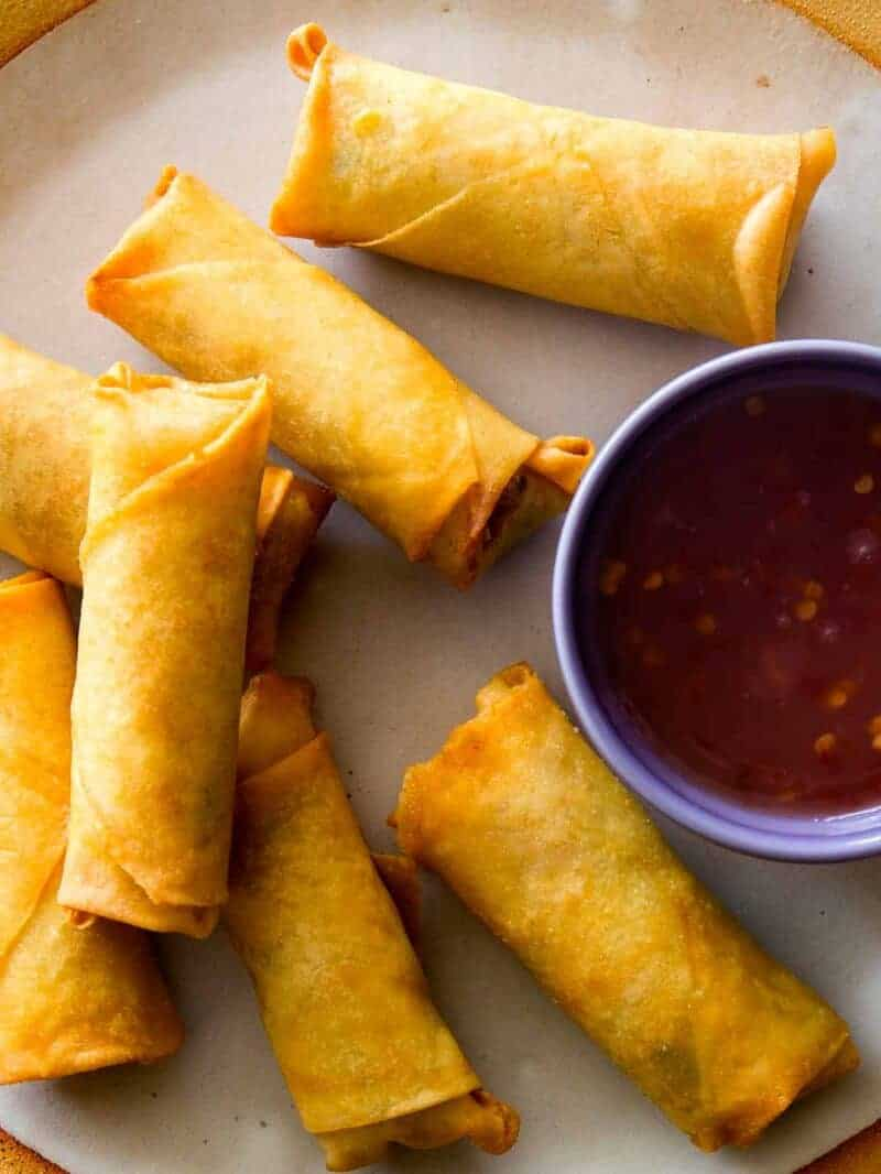 A close up on Vietnamese Style Pork and Shrimp Egg Rolls on a plate with sauce next to them.
