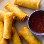 Egg rolls on a platter with a sweet and spicy sauce on the side.