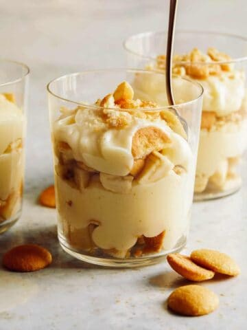 Three cups of banana pudding and one with a spoon in it.