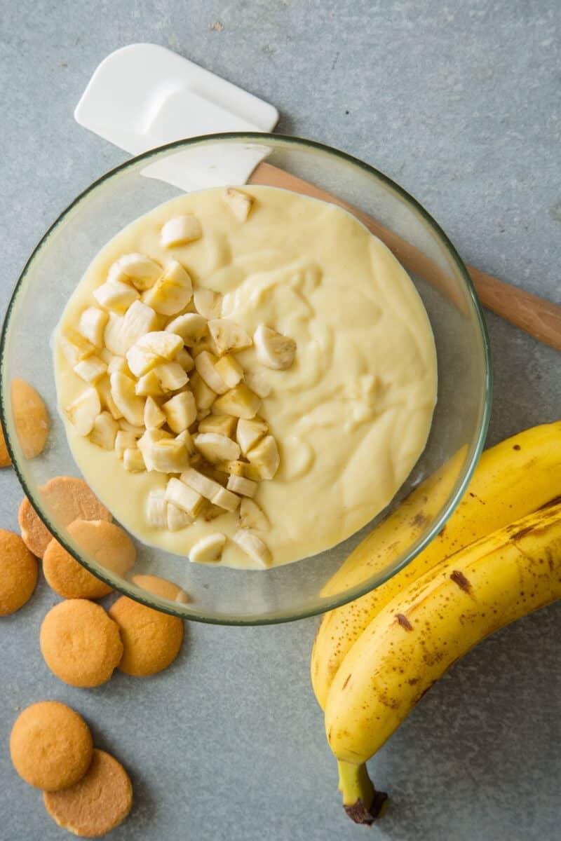 Banana pudding being folded with chunks of bananas.