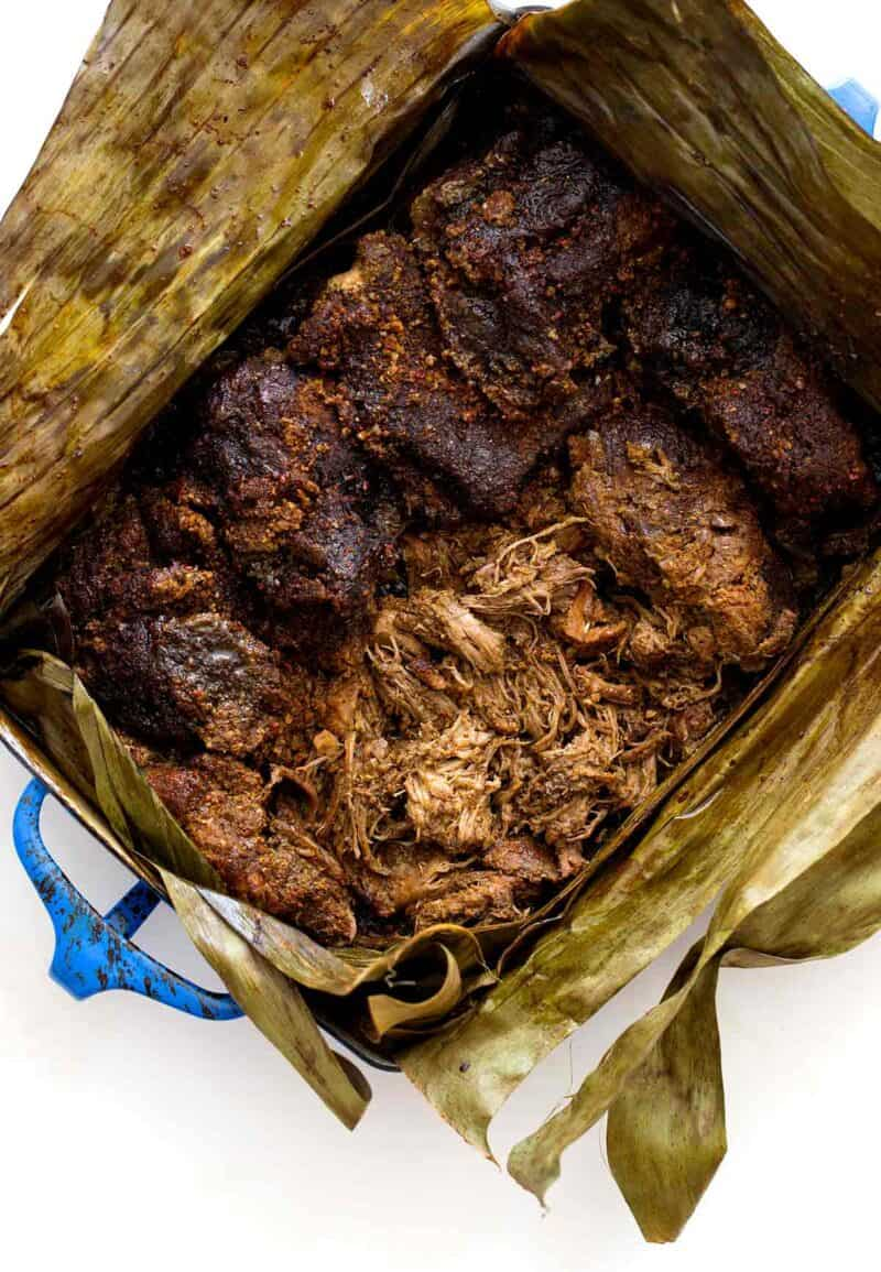 A pan of cochinita pibil in opened banana leaves to reveal the meat.