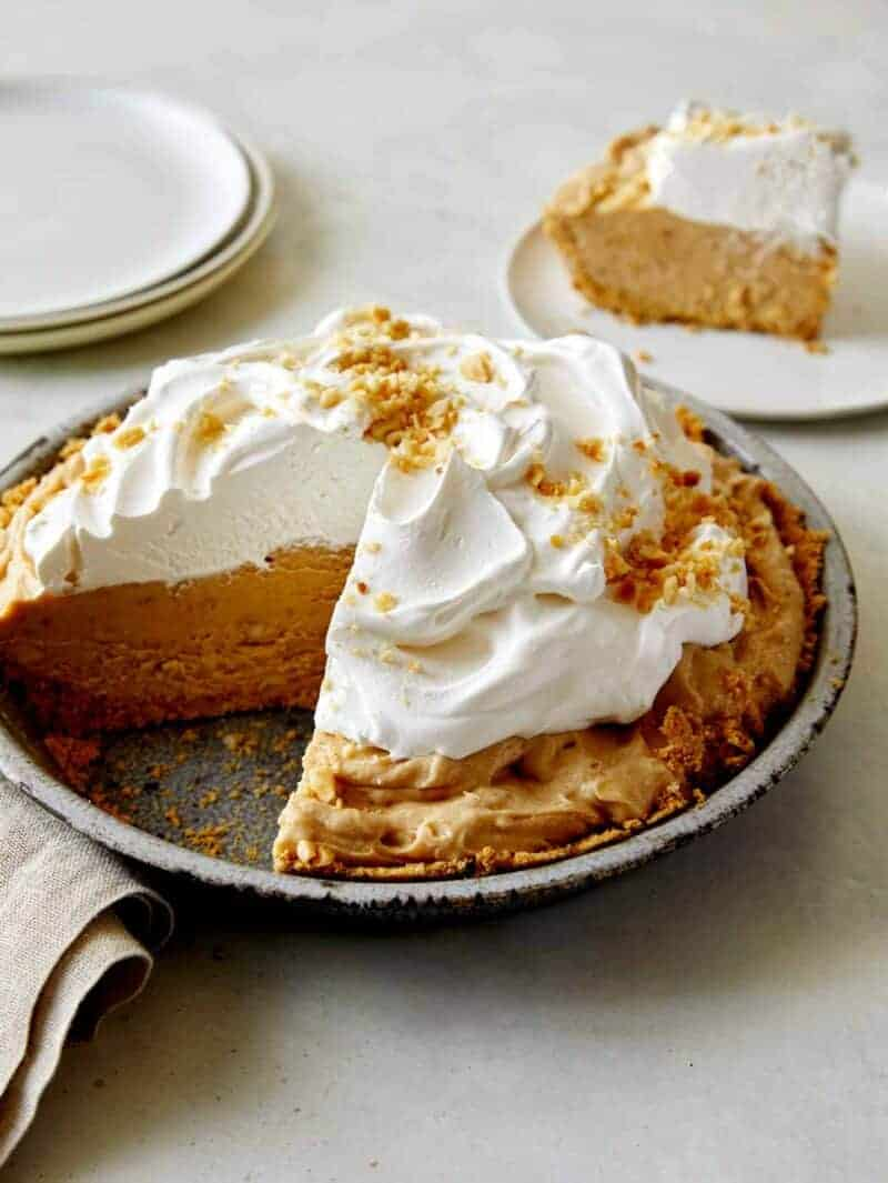 No Bake Peanut Butter Pie with whipped cream on top with a slice taken out.