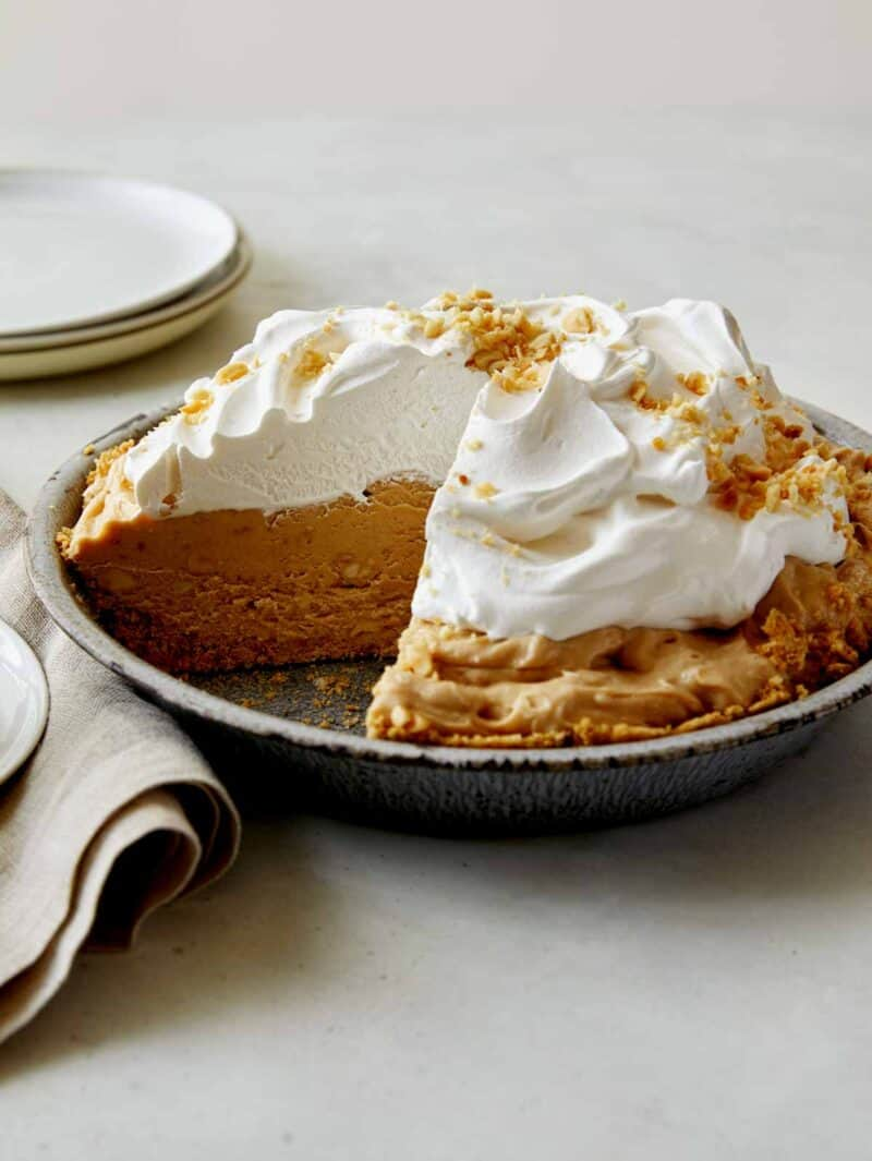 A creamy peanut butter pie with a slice taken out.
