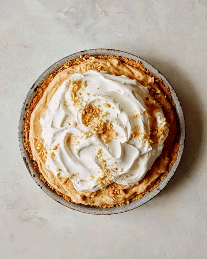 A creamy peanut butter pie with whipped cream on top and nuts.