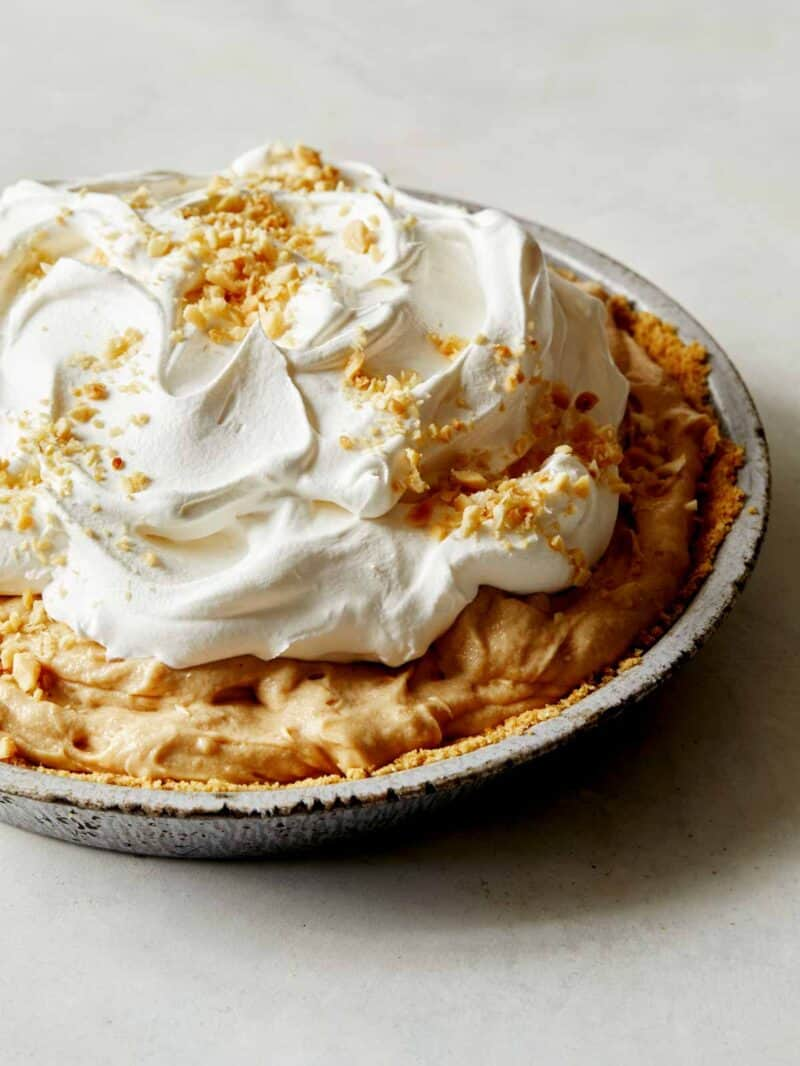 A close up on a creamy peanut butter pie with whipped cream, and nuts on top.