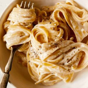 A recipe for one pot fettuccine alfredo in a bowl with a fork.