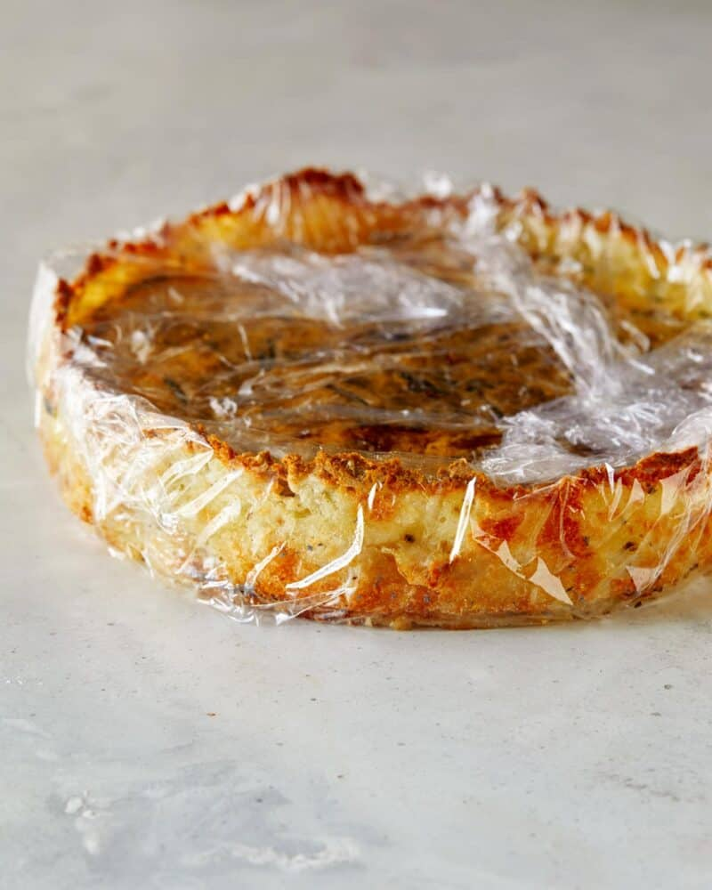 A hash brown quiche that is wrapped in plastic wrap.