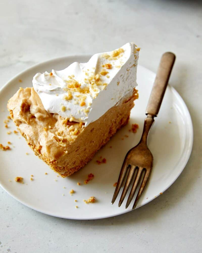 A slice of Creamy No Bake Peanut Butter Pie on a plate with a fork next to it.