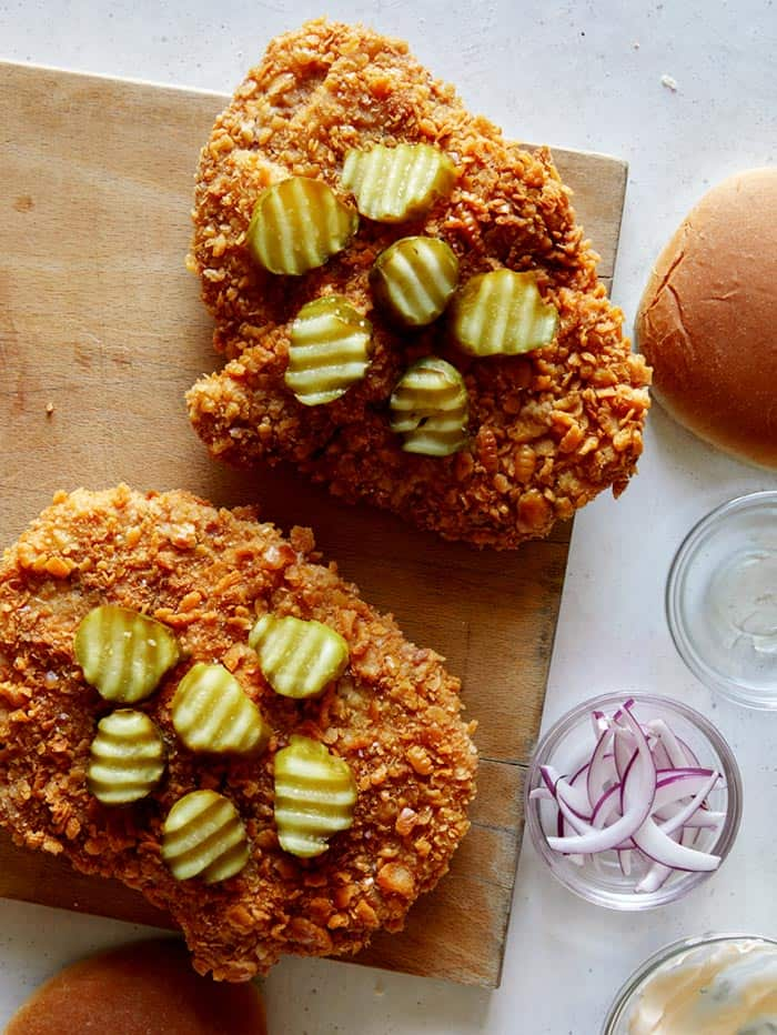 Building a pork tenderloin sandwich with pickles on top of the cutlet.