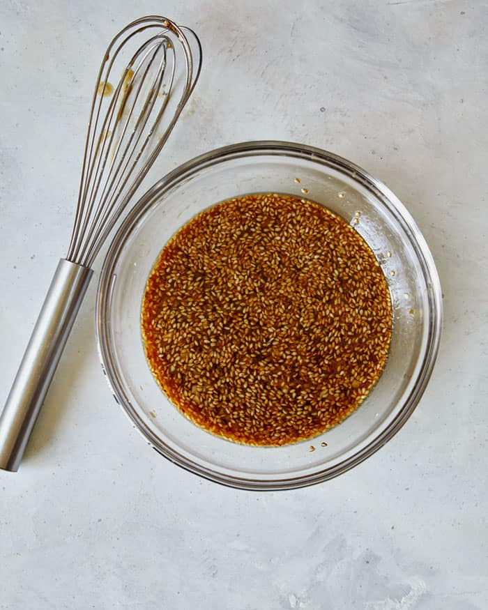 A bowl of sesame chicken sweet and sticky sauce in a mixing bowl with a whisk next to it.