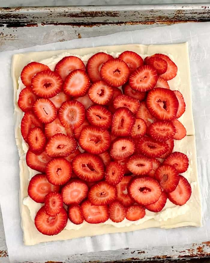 A puff pastry sheet layered with sliced strawberries.