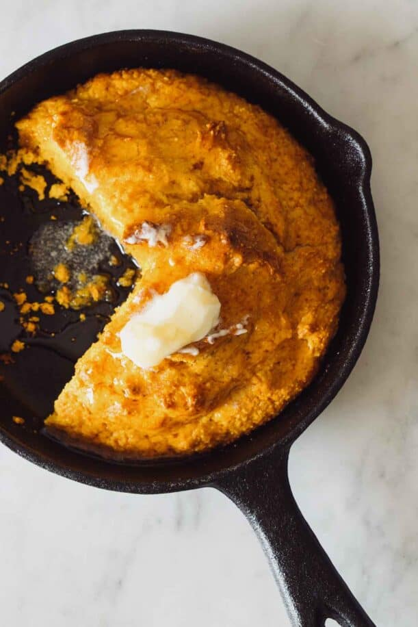 Pumpkin cornbread in a skillet with butter on top and honey.