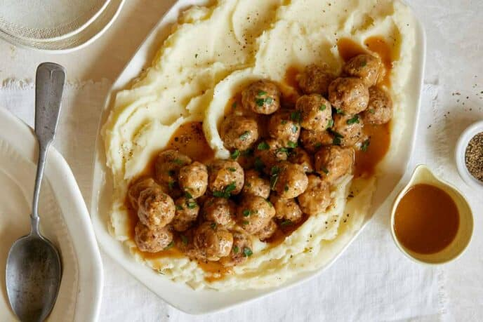 A platter of Swedish meatballs over mashed potatoes with plates to serve.