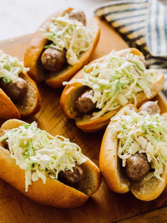 Bratwursts topped with slaw on a cutting board.