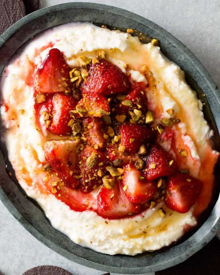 Honey whipped ricotta in a bowl topped with roastes strawberries and pistachios.