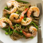 A bowl of sesame soba noodles with shrimp and a fork next to it.