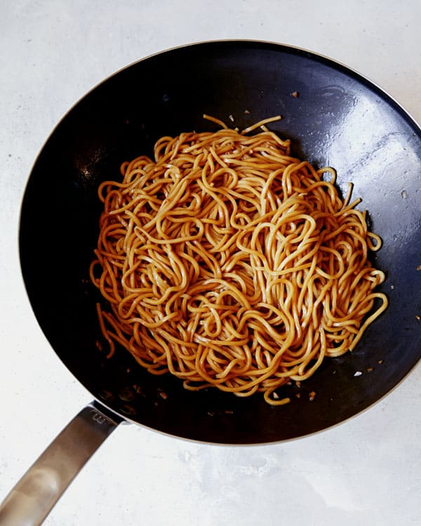 Gaelic noodle sauce tossed with noodles in a wok.
