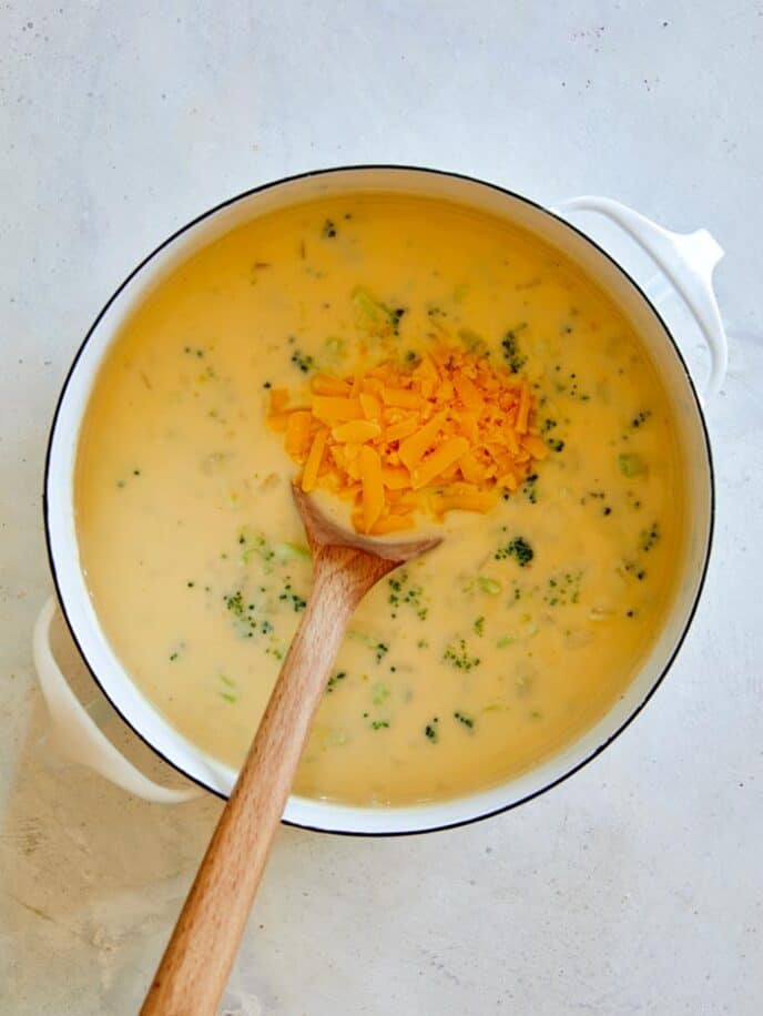 Adding in cheddar cheese to make broccoli cheddar soup.