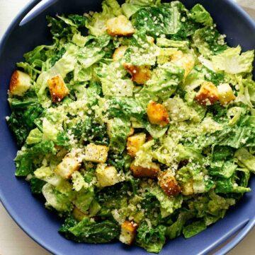 Classic caesar salad recipe in a blue serving dish.