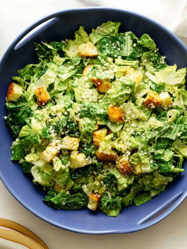 Classic caesar salad recipe in a blue serving dish.