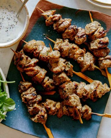 Lamb kabobs on a platter skewered with a side of yogurt sauce.
