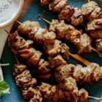 A platter of lamb kabobs with a salad next to it.
