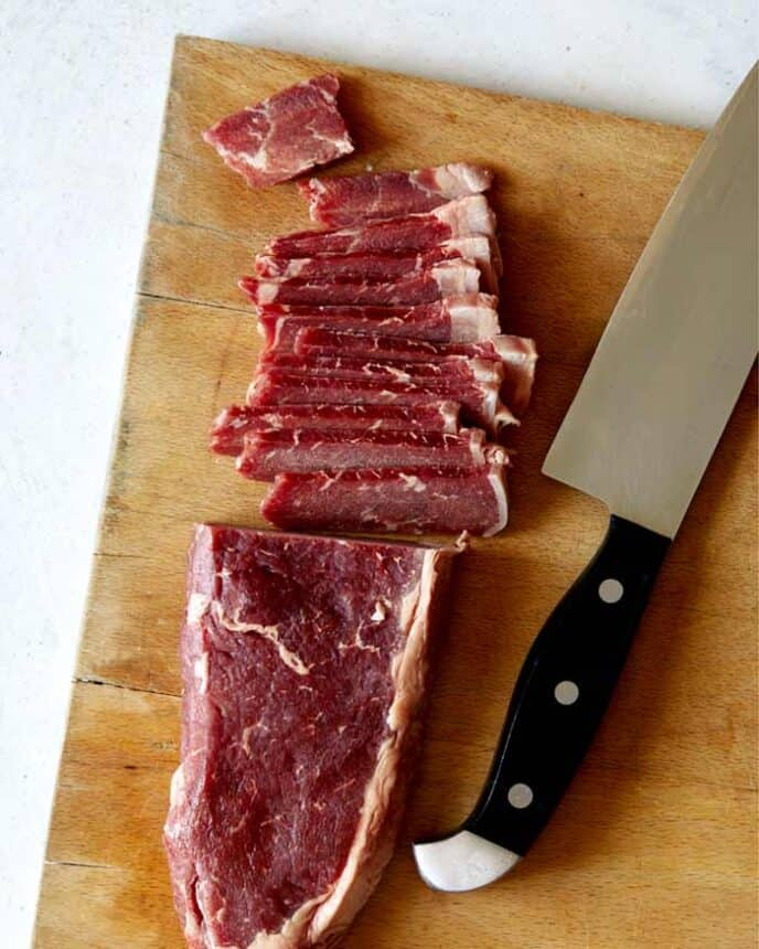 Slicing strip steak on a cutting board for Mongolian Beef.