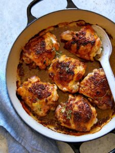 Oven baked chicken thighs with a spoon to serve.