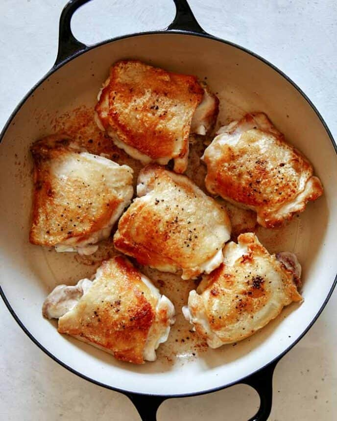 Seared and seasoned chicken thighs in a skillet.