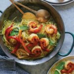 Singapore noodles recipe in a skillet being served onto two other plates.