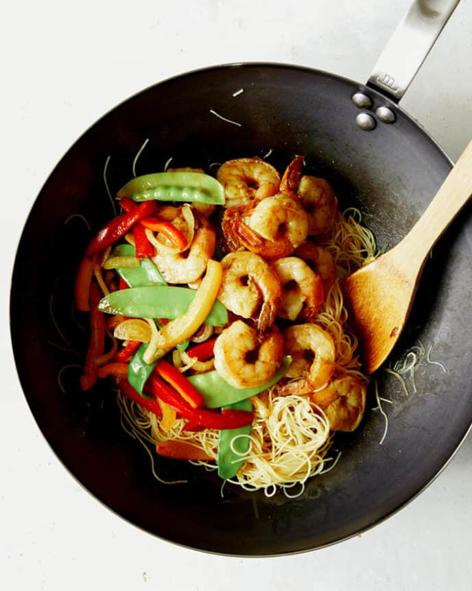 Singapore noodles recipe in a wok with shrimp and veggies.