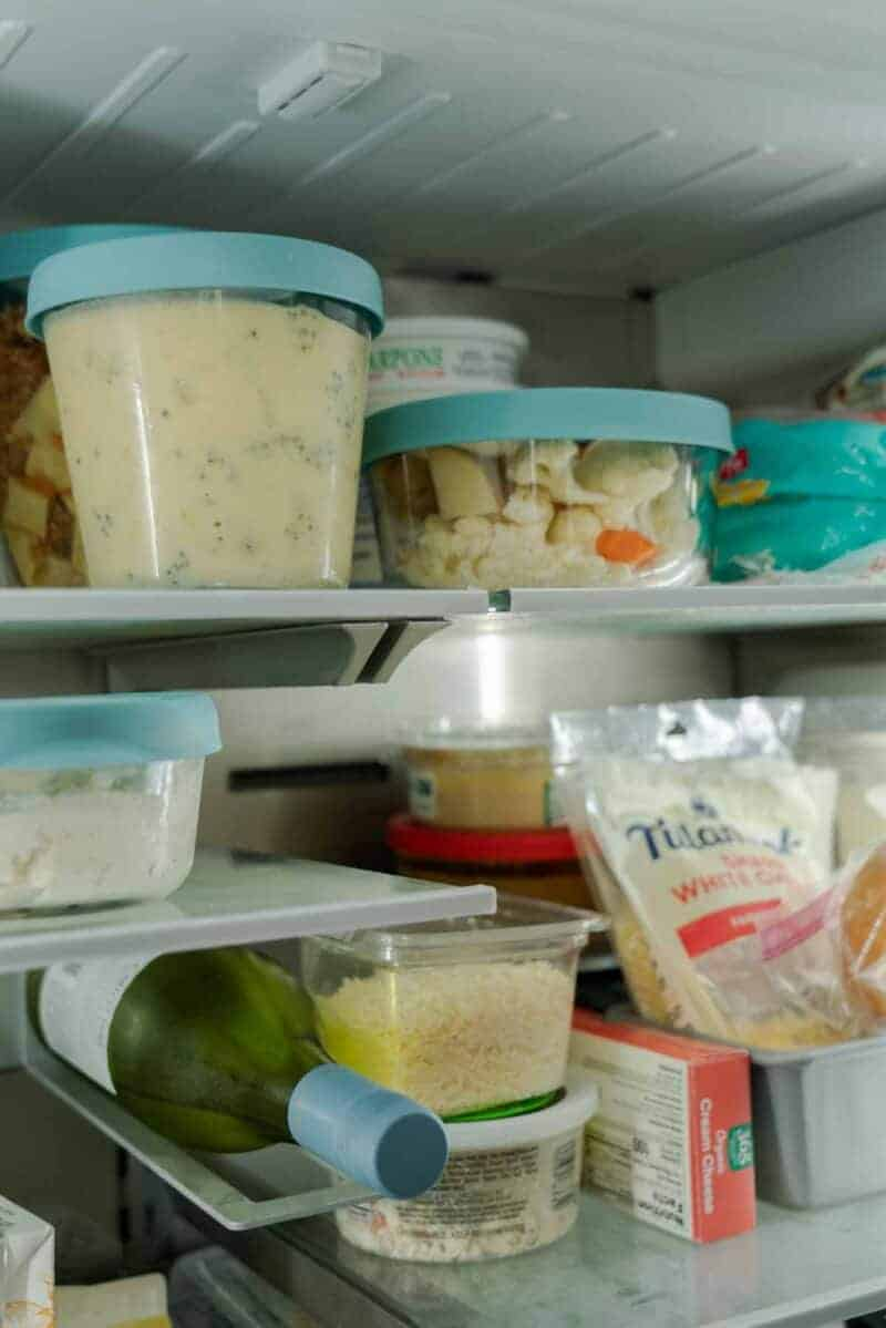 A close up view of the inside of a refrigerator and some tupperware.