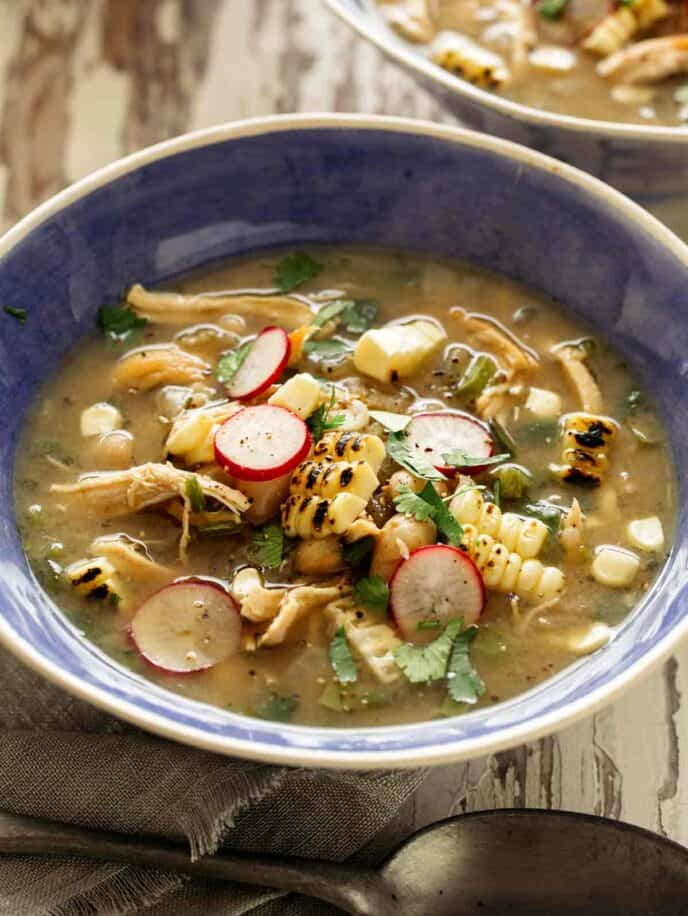 White bean chili in a blue bowl with toppings.